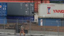 A workers passes cargo containers stacked up at the Port of Vancouver in Vancouver, B.C., in this file photo. (DARRYL DYCK/THE CANADIAN PRESS)