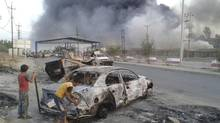 Civilian children stand next to a burnt vehicle during clashes between Iraqi security forces and al Qaeda-linked Islamic State in Iraq and the Levant (ISIL) in the northern Iraq city of Mosul, June 10, 2014. (REUTERS)