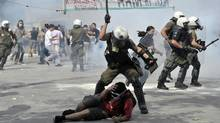 Protestors clash with riot police on June 15, 2011 during a demonstration near the parliament in the center of Athens (ARIS MESSINIS)