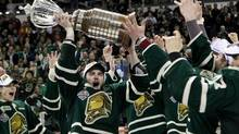 London Knights' captain Scott Harrington lifts the Ontario Hockey League Championship trophy after their 3-2 game seven win over the Barrie Colts, Monday May 13, 2013 in London, Ont. (Dave Chidley/THE CANADIAN PRESS)