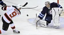Winnipeg Jets goaltender Ondrej Pavelec makes a save on New Jersey Devils' Bobby Butler during the first period of their NHL hockey game in Winnipeg February 28, 2013 (Reuters)