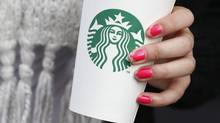A woman holds a Starbucks takeaway cup in this file photo. (SUZANNE PLUNKETT/REUTERS)
