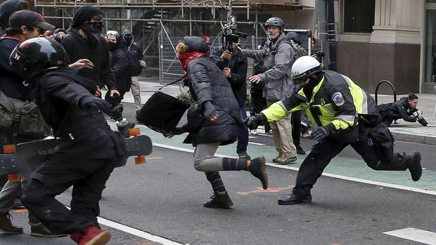 A police officer tries to tackle an anti-Trump protester on the sidelines of the inauguration.