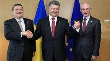 Ukraine's President Petro Poroshenko (C) poses with European Commission President Jose Manuel Barroso (L) and European Council President Herman Van Rompuy (R) at the EU Council in Brussels June 27, 2014. (STRINGER/REUTERS)