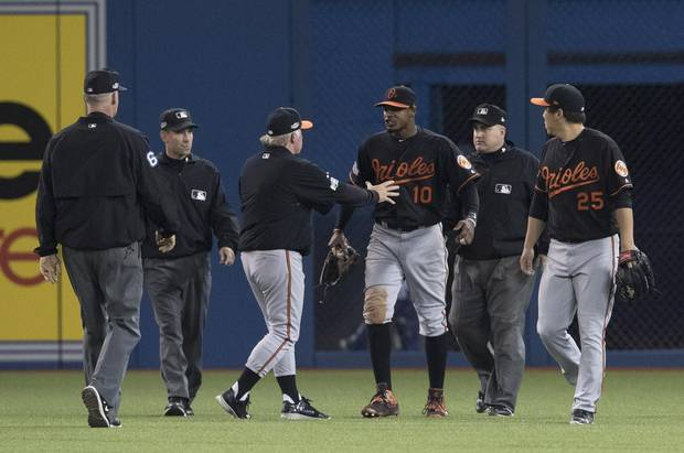 Umpires Ted Barrett, left to right, David Rackley, Baltimore Orioles manager Buck Showalter, Orioles' Adam Jones, umpire Eric Cooper and Orioles' Hyun Soo Kim talk after a beer was thrown onto the field during play following seventh inning on Tuesday.