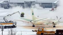 An airplane is sprayed with de-icing fluid prior to takeoff. (Matthias Schrader/AP)