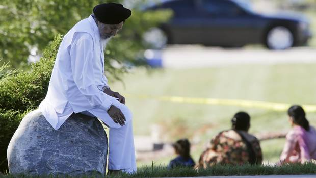 A man sits on a rock as police investigate the Sikh Temple of Wisconsin in Oak Creek, Wis., after a shooting Sunday, Aug 5, 2012. A gunman killed six people at the suburban Milwaukee temple in a rampage that left terrified congregants hiding in closets and others texting friends outside for help. The suspect was killed outside the temple in a shootout with police officers.