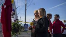 The family of Michael Lunn, one of two people who died in a shooting at the Western Forest Products mill, visit the growing makeshift memorial in Nanaimo, B.C., May 1, 2014. (John Lehmann/The Globe and Mail)