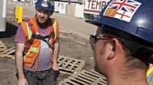 Temporary foreign worker David Beattie, left, from Scotland and Thomas Sutton from England take a break from working on the construction of a new police station in Edmonton. (Jason Franson For The Globe and Mail)