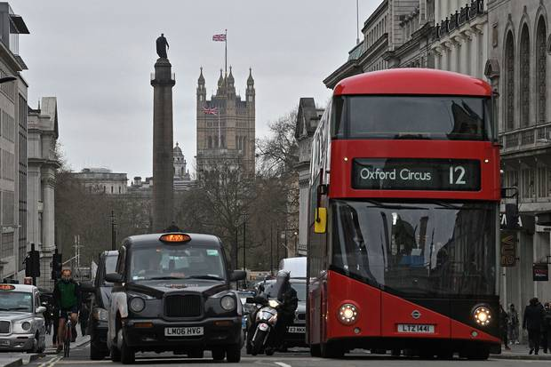 A red London bus waits at traffic lights in central London on March 20, 2017. London is trying out a system of bus-mounted cameras to monitor car use and issue tickets.