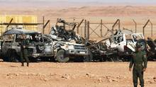 Algerian soldiers stand near damaged cars used by Islamist militants during a siege earlier this month near the Tiguentourine Gas Plant in In Amenas, 1600 kilometres southeast of Algiers, Jan. 31, 2013. (LOUAFI LARBI/REUTERS)