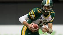 Edmonton Eskimos' Mike Reilly rushes for a first down against the B.C. Lions during the first half of a CFL football game in Vancouver on Saturday, June 28, 2014. (DARRYL DYCK/THE CANADIAN PRESS)