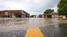 Water floods the streets in downtown High River, Alta., on June 20, 2013. (CHRIS BOLIN FOR THE GLOBE AND MAIL)