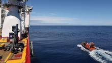 Crew members are seen aboard a fast response craft (R) from the Australian Defence Vessel Ocean Shield (L) as they continue to search for debris of the missing Malaysian Airlines flight MH370 in the southern Indian Ocean, in this picture released by the Australian Defence Force on April 8, 2014. (HANDOUT/REUTERS)