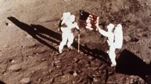"In this July 20, 1969 file photo, Apollo 11 astronauts Neil Armstrong and Edwin E. ""Buzz"" Aldrin, the first men to land on the moon, plant the U.S. flag on the lunar surface. (Anonymous/The Associated Press)"
