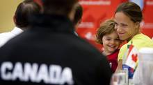 Heptahtlete and hurdler, Jessica Zelinka, right, from London, Ont., hugs her daughter Anika, three years-old, as she listens to Athletics Canada announce the members of Team Canada for the track and field portion of the 2012 London Olympics at a news conference in Calgary, Alta., Sunday, July 1, 2012. Sixty four athletes were named to the team. (Jeff McIntosh/THE CANADIAN PRESS)