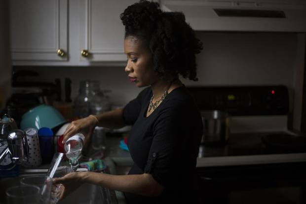 Shanice Ollie washes dishes with boiled bottled water, a process that can take an hour or more, at her home in Flint, Mich., March 5, 2016. Though lead levels in Flint's tap water have decreased slightly over the last six months, residents are urged to continue using bottled water and filters for drinking, researchers said on April 12.