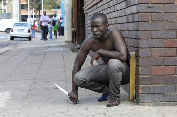 A foreign national holds a knife after clashes between a group of locals and police in Durban on April 14 ,2015, amidst ongoing violence against foreign nationals living in the South African city. In recent years, South Africa has deported as many as 54,000 people annually, almost exclusively to African countries.