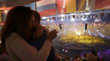 A couple embraces after the Olympic Flame was lit during the opening ceremony of the London 2012 Olympic Games at the Olympic Stadium July 27, 2012. (Reuters)