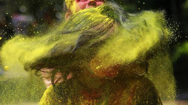 An Indian woman shakes her head covered in coloured powder as she celebrates Holi, the Hindu festival of colors, in Mumbai India, Monday, March 17, 2014. The festival heralds the arrival of spring. (Rafiq Maqbool/AP)