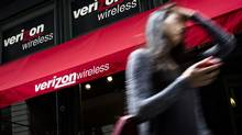 A pedestrian uses her cell phone as she passes a Verizon Wireless store on Broadway in Lower Manhattan, Thursday, June 6, 2013, in New York. Verizon's CFO confirmed to the Wall Street Journal on Tuesday that the company is in the preliminary stages of weighing entry into the Canadian market. (John Minchillo/AP)