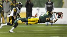 Edmonton Eskimos' Fred Stamps (R) makes a diving reception in front of Hamilton Tiger-Cats' Marc Beswick during their CFL game in Edmonton October 5, 2012. (DAN RIEDLHUBER/REUTERS)