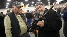 Gun owners discuss a potential sale of an AR-15, one of the most popular and controversial weapons, during the 2013 Rocky Mountain Gun Show at the South Towne Expo Center in Sandy, Utah Saturday, Jan. 5, 2013. In spite of the recent school shooting in Newtown, Conn., gun enthusiasts packed in by the hundreds to purchase weapons and ammunition. The gunman in the Sandy Hook Elementary School shooting in December used an AR-15 to kill 20 first-graders and six educators in the school before killing himself as police closed in. (Ben Brewer/AP)