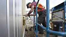 Temporary foreign worker David Beattie, from Scotland installs cladding while working on the construction of a new police station in Edmonton, Monday April 30, 2012. (Jason Franson for The Globe and Mail)