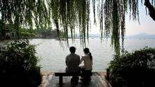 CHINA. Hangzhou. A young couple sit next to the famous West Lake. 2009 (Sean Gallagher Photography)