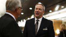 Suncor CEO Steve Williams, right, talks to a shareholder at the company's annual general meeting in Calgary, May 1, 2012. (TODD KOROL/REUTERS)