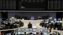Traders work at their desks in front of the Dax board at the Frankfurt stock exchange June 22, 2012. (TOBIAS SCHWARZ/REUTERS)