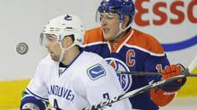Edmonton Oilers' Shawn Horcoff, right, battles with Vancouver Canucks' Kevin Bieksa, during the first period of the NHL hockey game in Edmonton on Sunday, February 19, 2012. The Canucks won 5-2. THE CANADIAN PRESS/John Ulan (John Ulan)