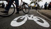 A cyclists walks by a bike lane symbol painted by activists at a memorial on Monday, November 14, for pregnant cyclist Jenna Morrison, who was recently killed after being struck by a truck at Sterling and Dundas in Toronto. (Michelle Siu/The Globe and Mail/Michelle Siu/The Globe and Mail)