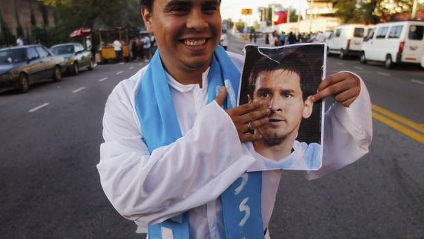 A fan of Argentina, dressed up as Pope Francis, poses with a photo of Argentine striker Lionel Messi as he arrives at Monumental stadium for the 2014 World Cup qualifying soccer match against Venezuela in Buenos Aires, March 22, 2013. REUTERS/Marcos Brindicci (Marcos Brindicci/REUTERS)