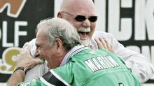 Prime Minister Paul Martin playfully blocks Saskatchewan Roughrider football team President Jim Hopson during a Roughrider practice session in Regina Tuesday, August 22, 2005. (CP PHOTO/Fred Chartrand) (FRED CHARTRAND)