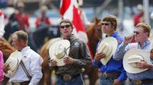 Cowboys hold their hats to their hearts as the national anthem is played before the start of the rodeo at the Calgary Stampede on July 10, 2012. (Todd Korol For The Globe and Mail)