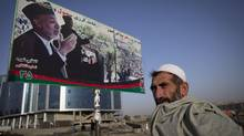 An Afghan stands in front of a poster of President Hamid Karzai in Kabul. (Paula Bronstein/2009 Getty Images)