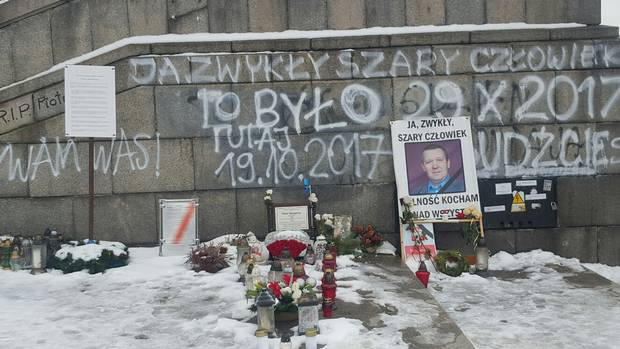 Outside Warsaw's Palace of Culture, a makeshift memorial honours Piotr Szczesny, who lit himself on fire last October to protest against Poland's right-wing government.