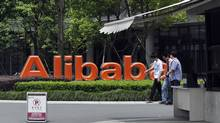 Young men walk past the corporate logo at the headquarters compound of Alibaba Group in Hangzhou in eastern China's Zhejiang province Monday May 21, 2012. (AP)