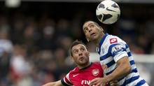 Queens Park Rangers' Tal Ben Haim, right watches the ball as he attempts to block Arsenal's Santi Cazorla during their English Premier league soccer match at Rangers' Loftus road stadium in London, Saturday, May 4, 2013. (Associated Press)