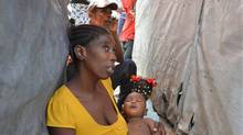 In this June 30, 2014 photo, Evelyn Melisma holds her 7-month-old baby outside their tent home in Port-au-Prince, Haiti, as his fever spikes with a newly arrived mosquito-borne illness. (David McFadden/AP)