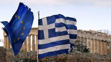 The Parthenon on the Athens Acropolis is seen behind a Greek and an EU flag atop the Greek ministry of finance February 8, 2012. (YANNIS BEHRAKIS/Yannis Behrakis/Reuters)