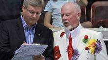 Prime Minister Stephen Harper sketches out a play while coaching with Don Cherry during Hockey Night in Barrie, a fundraiser for the local hospital, on Aug. 12, 2010. (Darren Calabrese/THE CANADIAN PRESS)