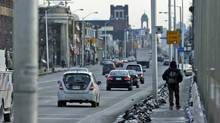 A pedestrian walks across the Bloor Street viaduct into Toronto's Danforth neighbourhood. The federal riding was held by NDP leader Jack Layton from 2004 until his death in August of 2011. (Louie Palu/Louie Palu/The Globe and Mail)