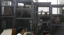 Muslim Brotherhood's General Guide Mohamed Badie, right, is pictured in a defendant's cage with other defendants in a courtroom in Cairo June 7. (MOHAMED ABD EL GHANY/REUTERS)