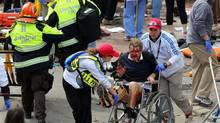Medical workers aid injured people at the 2013 Boston Marathon following an explosion in Boston, Monday, April 15, 2013. Two explosions shattered the euphoria of the Boston Marathon finish line on Monday, sending authorities out on the course to carry off the injured while the stragglers were rerouted away from the smoking site of the blasts. (David L. Ryan/AP)