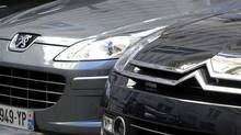 In this Sept. 7, 2012 file photo, a Peugeot, left, and Citroen cars are parked in Paris. (Jacques Brinon/AP)
