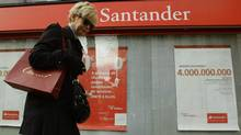 A woman walks past a Santander bank branch in central Madrid in a file photo. Spain's central bank lifted penalties on high interest offers in August. (ANDREA COMAS/REUTERS)