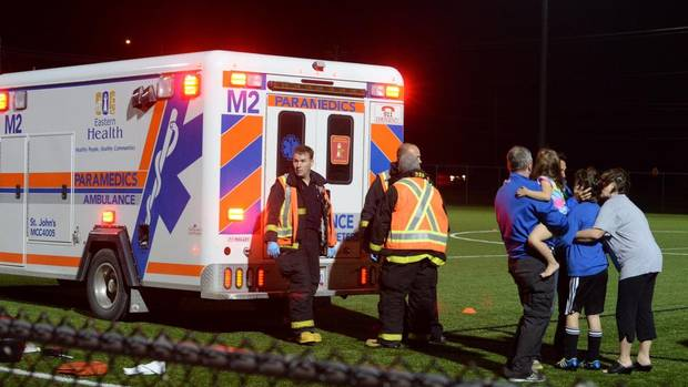Parents and children hug each other after an eleven-year-old boy is put into an ambulance in Topsail, Nfld., 23 kms west of St. John's, on Thursday Sept. 25, 2014. The child was apparently stabbed in the neck during a soccer fun night at the local field. A person of interest has been taken into custody by the Royal Newfoundland Constabulary. (Keith Gosse/THE CANADIAN PRESS)