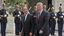 French President Francois Hollande, left, welcomes Prime Minister Stephen Harper upon his arrival at the Elysee Palace in Paris on Thursday. (Francois Mori/Associated Press)